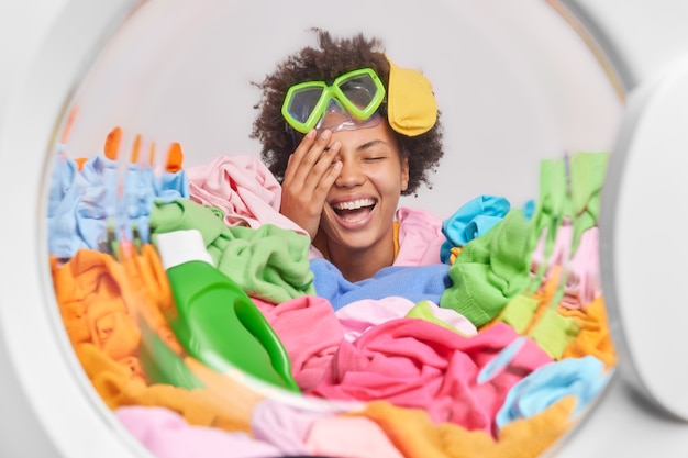 Overjoyed curly haired young woman stands in pile of multicolored laundry does washing at home wears snorkeling mask has sock on head white wall