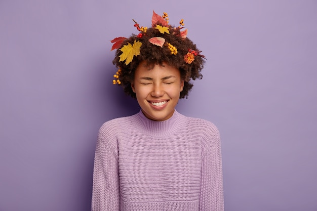 大喜びの巻き毛の女性は前向きに笑い、秋の気分を持ち、広く笑顔で、友達と冗談を言い、黄色いカエデの葉とナナカマドの果実を髪に、カジュアルな服を着ています。幸福、幸福