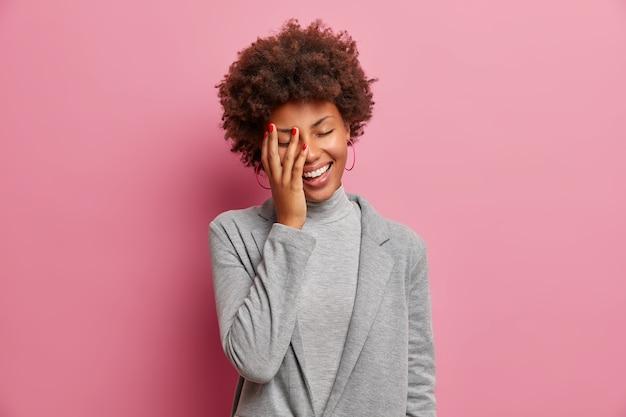 기뻐하는 어두운 피부의 여성 기업가는 긍정적으로 웃고, 눈을 감고 서고, 웃기는 농담을 웃으며, 손바닥을 만들고, 우아하게 옷을 입고, 하얀 치아를 보여줍니다.