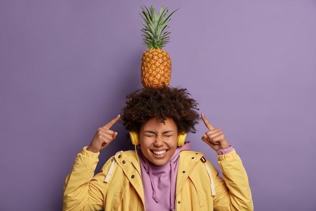 Ragazza dalla pelle scura felicissima trasporta ananas esotico sulla testa ride ascolta positivamente musica in cuffie stereo vestite casualmente andando a mangiare frutta fresca, sciocchi in giro, isolato sopra il muro viola