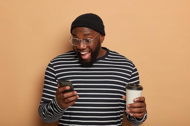 Обрадованный темнокожий парень сосредоточился в смартфоне