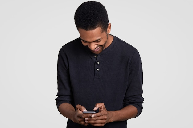 Overjoyed dark skinned man with afro haircut, laughs happily, holds cell phone, reads funny story on cellular, types feedback