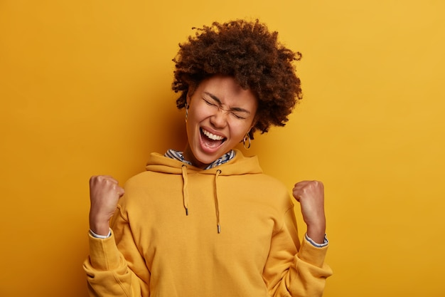 Overjoyed dark skinned woman celebrates achievement, clenches fists and feels triumph, feels empowered, watches tv game, happy favorite team scored goal, exclaims hooray, tilts head, wears hoodie