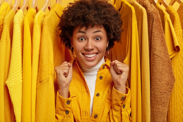 기뻐하는 짙은 피부색의 여성은 주먹을 쥐고, 옷장 갱신을 기뻐하며, 옷걸이에 노란색 옷차림 사이에 서고, 탈의실에 서 있습니다. 사람과 패션 컨셉