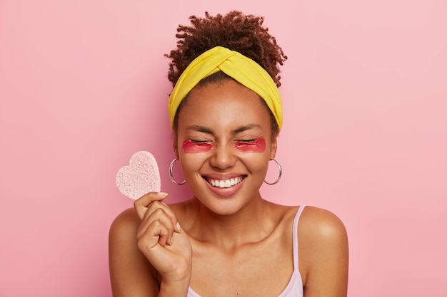 Overjoyed dark skinned woman closes eyes, wears facial patches under eyes, feels relieved and satisfied, holds cosmetic sponge in form of heart, models against pink wall. natural beauty