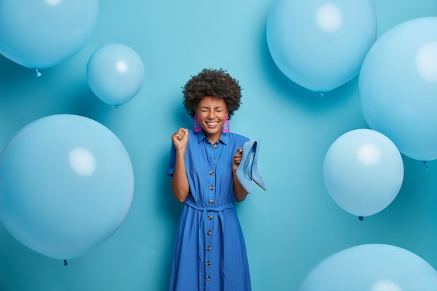 Overjoyed dark skinned woman happy to have special occasion for wearing stylish high heeled shoes, poses against blue wall with balloons, clenches fist and feels upbeat. fashion photo