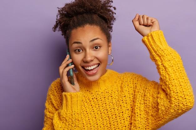 Una donna dalla pelle scura felicissima ha una conversazione mobile positiva, ascolta ottime notizie, alza il braccio e balla dalla gioia