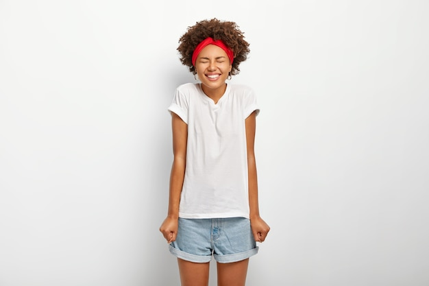 Overjoyed dark skinned woman with afro hair keeps hands clenched in fists, enjoys long awaited holidays, dressed in casual summer outfit, expresses good emotions, isolated on white background