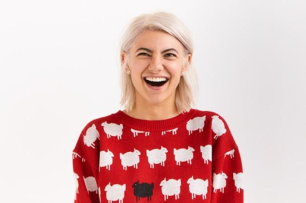 입을 크게 벌리고 넓은 미소를 지으며 큰 소리로 웃으며 즐거워하는 황홀한 여성. 진정성 있고 긍정적 인 인간의 감정, 반응 및 감정