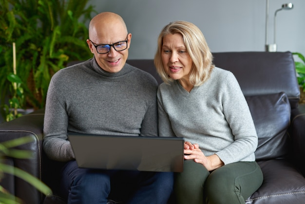 Overjoyed elderly mother sit rest on sofa with grown-up son watch funny video on modern laptop