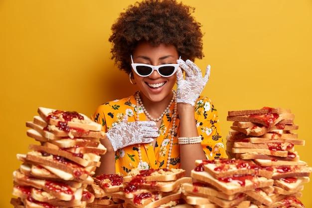아프로 머리 미소를 지닌 기뻐 우아한 아가씨는 맛있는 샌드위치 더미에 대해 세련된 선글라스 포즈를 행복하게 착용합니다.