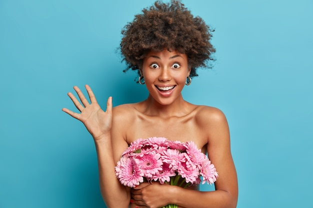 Overjoyed emotional curly haired lady holds bouquet of flowers, raises palm, covers naked body, has bugged eyes and toothy smile, well cared heathy dark skin,
