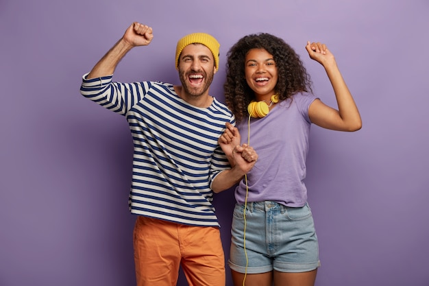 Overjoyed energetic millennial multiethnic woman and man have fun together, listen to music, raise clenched fists, move with rhytm, laugh and pose against purple background