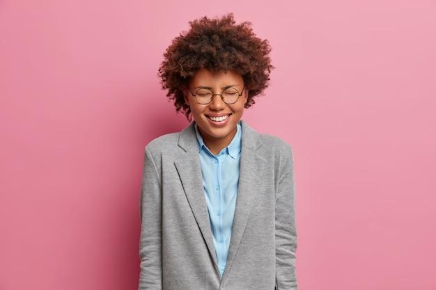Imprenditore felicissimo si rallegra per l'affare di successo, ride ad alta voce, chiude gli occhi, indossa una giacca grigia formale, esprime emozioni positive