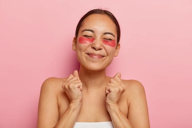 Una femmina etnica felicissima stringe i pugni con trionfo, gode della routine quotidiana di coccole, si prende cura della pelle, usa bende sugli occhi, chiude gli occhi dal piacere ricevuto durante i trattamenti di bellezza, posa al coperto