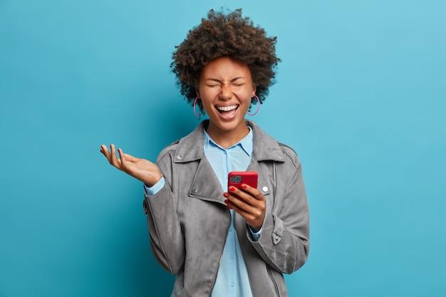곱슬 머리를 가진 기뻐하는 민족 여성, 스마트 폰에서 재미있는 비디오를 보며 웃고, 눈을 감고 손을 들고, 기분이 좋고, 회색 캐주얼 재킷을 입고, 포즈를 취합니다.