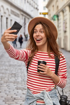 帽子をかぶった大喜びのヨーロッパの女性旅行者は、屋外で自分撮りの肖像画を作り、古代の町での遠足中に楽しんでいます