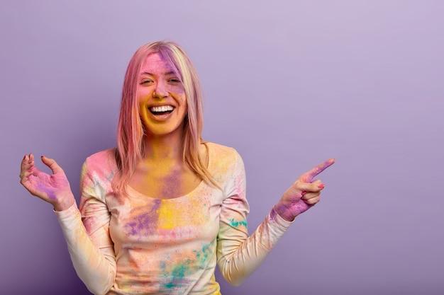 大喜びのヨーロッパ人女性がポジティブな印象で笑い、ホーリー祭が開催される場所を示し、色のついた粉を楽しんだり、色とりどりの染料を塗ったり、笑顔を広げたりします。インドでのお祝い