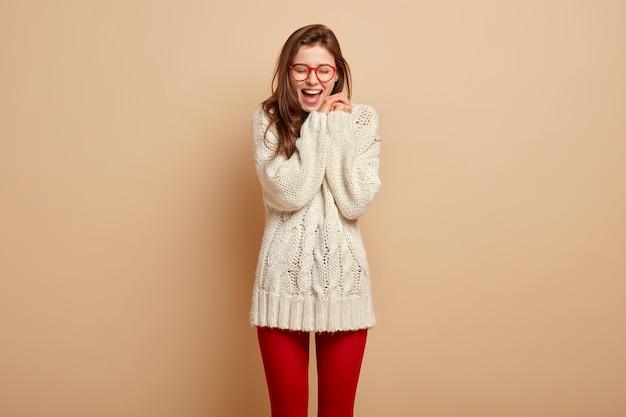 La donna europea felicissima ride sinceramente, tiene le mani unite vicino al viso, tiene la bocca aperta, soddisfatta delle notizie positive