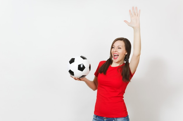 유럽 젊은 여성, 재미있는 조랑말 꼬리 2개, 축구 팬 또는 흰색 배경에 격리된 클래식 축구공을 들고 빨간색 유니폼을 입은 선수. 스포츠 축구 건강, 건강한 라이프 스타일 개념입니다.
