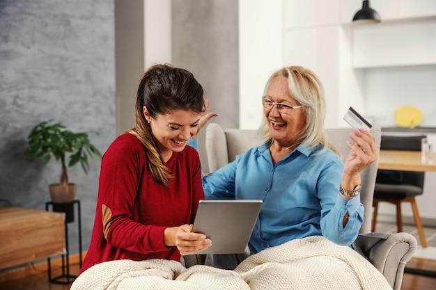 一緒に家に座って、オンラインショッピングにタブレットを使用している大喜び、興奮した母と娘。クレジットカードを保持している母親とタブレットを保持している娘。母は何か面白いものを見つけました。