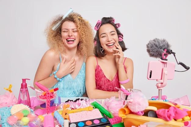 大喜びの女性の美容ブロガーは、白い背景の上に分離されたさまざまな化粧品に囲まれた特別な機会のためにドレスを着て髪型を一緒に楽しんで一緒に楽しく笑うビデオを記録します
