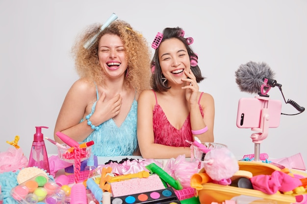 Overjoyed female beauty bloggers record video laugh happily have fun together wear dress and do hairstyle for special occasion surrounded by different cosmetic products isolated over white background