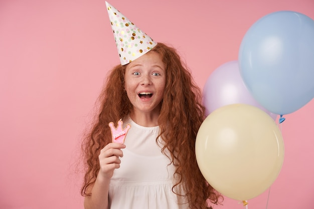Una ragazzina felicissima con i capelli ricci rossi che indossa abiti festivi con palloncini colorati, guardando felicemente alla telecamera con le sopracciglia alzate, esprime vere emozioni positive