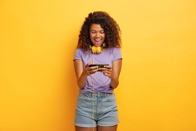 Обрадованная женщина играет на смартфоне, увлечена онлайн-играми, свободное время проводит с современными технологиями.
