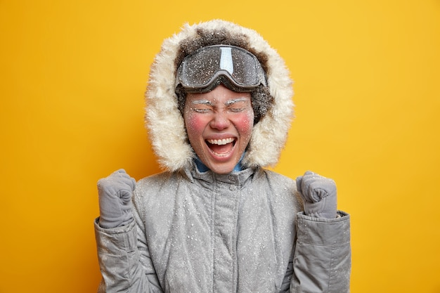 Overjoyed female skier enjoys winter time raises clenched fists and celebrates having awesome day exclaims with joy wears winter clothing.
