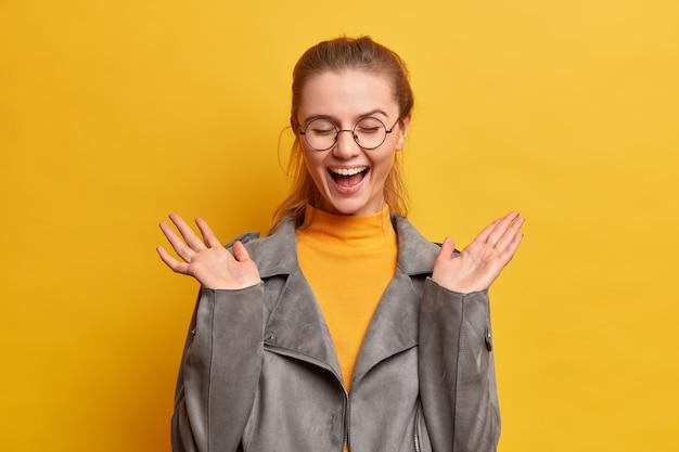 大喜びの女性のティーンエイジャーは幸せに笑い、手を上げ続け、満足から目を閉じます