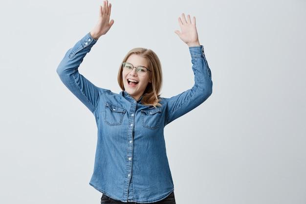Обрадованная женщина носит рубашку даним, стильные очки, волнующие жесты, громко восклицает от удивления, радуясь встрече со старым другом, поднимает руки вверх. блондинка радуется успеху на работе.