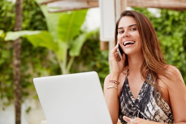 魅力的な外見を持つ個人的なウェブサイトを監視する大喜びの女性の若いブロガー、携帯電話で友人と成功を共有し、無料のワイヤレスネットワークに接続している多くのフォロワーがいることを誇りにしています