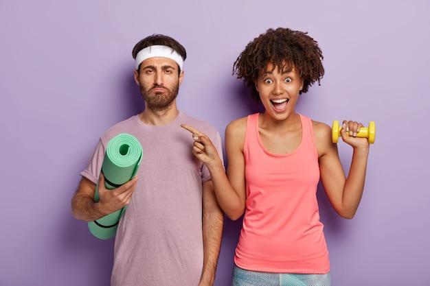 大喜びのフィット女性は、深刻な疲れた表情の男性を指差して、スポーツ用品を持って、上腕二頭筋を訓練し、インストラクターと一緒にヨガのトレーニングを受けます。ジムのカップル