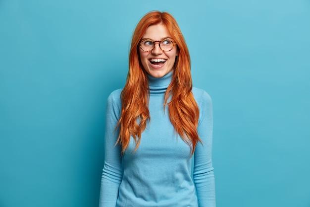 ヨーロッパの外観を持つ大喜びの生姜の若い女性は大声で笑い、楽しみを持っており、光学メガネのカジュアルなタートルネックを身に着けている素敵なイベントを喜んでいます。