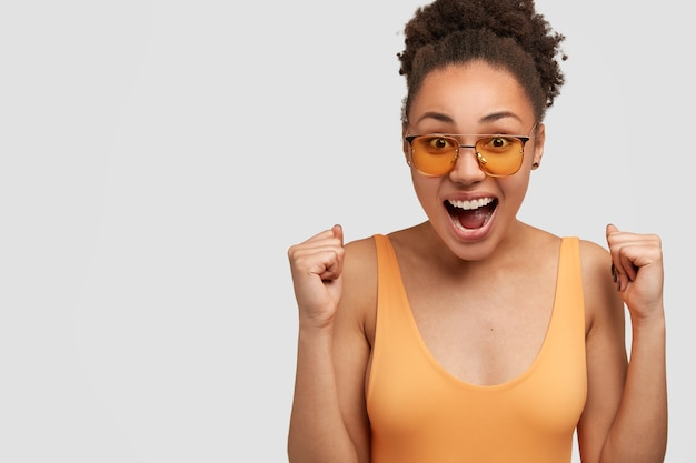 Overjoyed glad dark skinned woman with happy expression