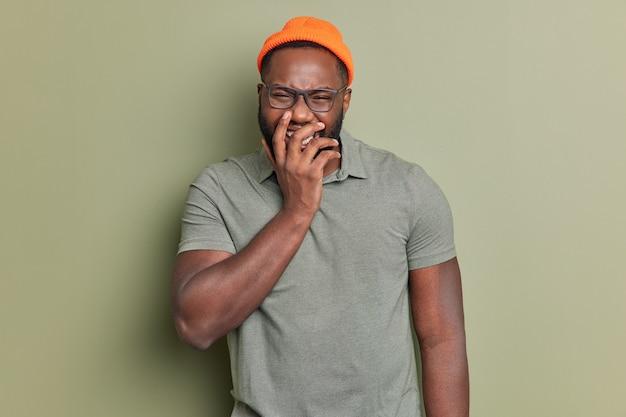 어두운 피부를 가진 기뻐하는 남자가 입을 가리고 행복하게 웃으며 즐겁게 웃고 스튜디오에서 캐주얼 한 옷을 입은 재미있는 것을 듣는다.