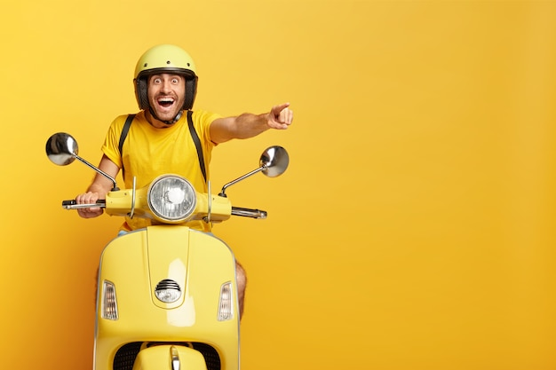 Overjoyed guy with helmet driving yellow scooter