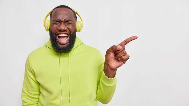 Overjoyed handsome male model with dark skin and thick beard laughs out from positive emotions points away shows something funny listens to music via headphones wears green hoodie poses indoor