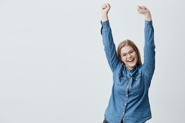 Overjoyed happy blonde woman gestures actively being surprised to recieve unexpected gift from boyfriend, raises arms in the air, has excited expression. people and positve emotions concept.