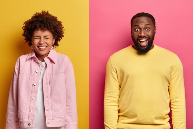 기뻐하고 행복하고 어두운 피부를 가진 여자와 남자는 긍정적 인 것에서 웃고, 캐주얼 한 옷을 입고, 노란색과 분홍색 벽에 서서 좋은 감정을 표현합니다. 민족성, 분위기 및 기쁨 개념