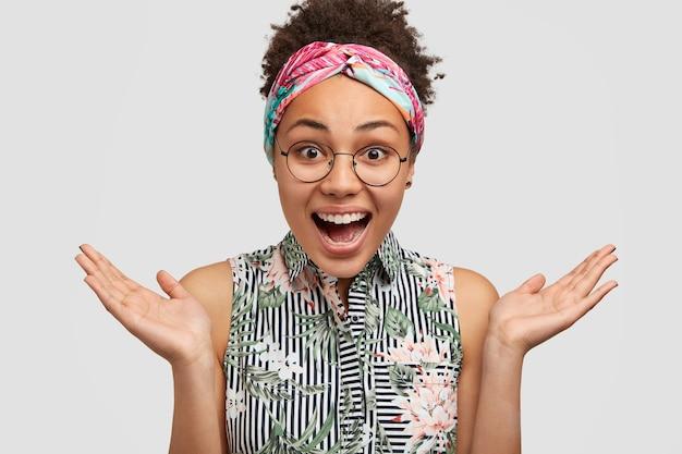 大喜びの幸せな暗い肌の若い魅力的な女性は手のひらを上げ、広い笑顔を持っています