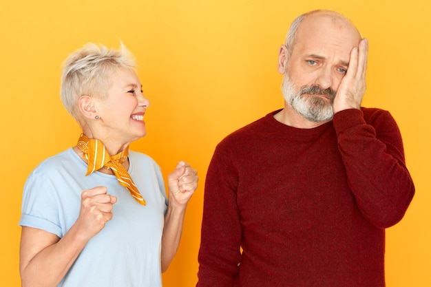 Overjoyed happy middle aged woman with blonde pixie hair clenching fists in excitement winning in lottery, her sad upset senior husband with beard holding hand on his cheek, having depressed look