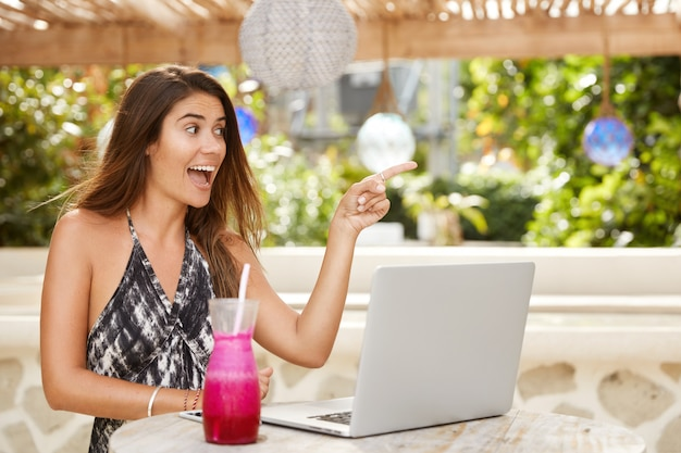 Overjoyed happy woman points joyfully somewhere, sits in front of opened laptop computer, woks remotely, drinks fresh smoothie, spends free time in cozy terrace cafe. people and lifestyle concept