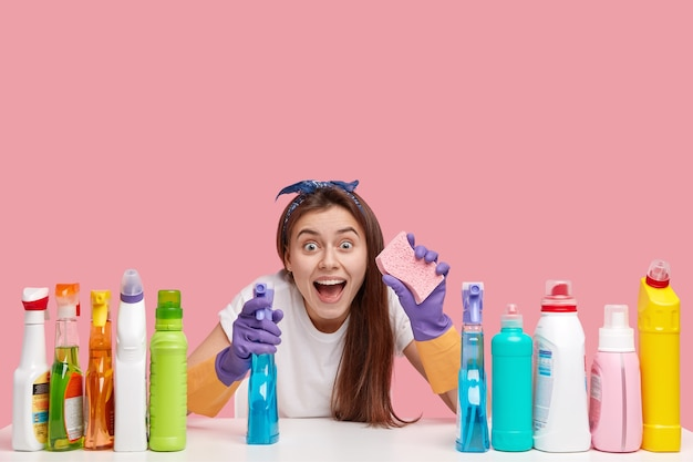 Overjoyed happy young lady keeps mouth opened, carries spray and sponge, looks in amazement, uses multipurpose detergents for scrubing
