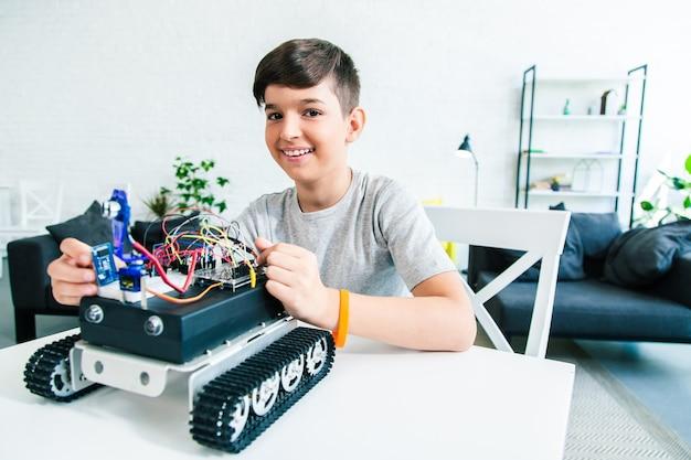 로봇을 만드는 동안 엔지니어링 프로젝트를 준비하는 독창적인 남학생