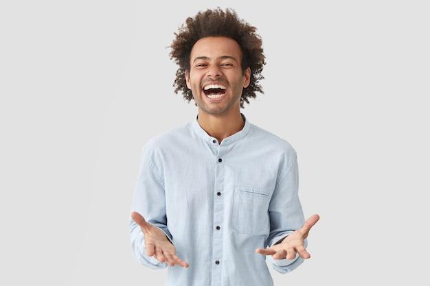 大喜びのうれしそうな魅力的な男の学生は、口を大きく開け、楽しく笑い、前向きさを表現し、エレガントなシャツを着ています