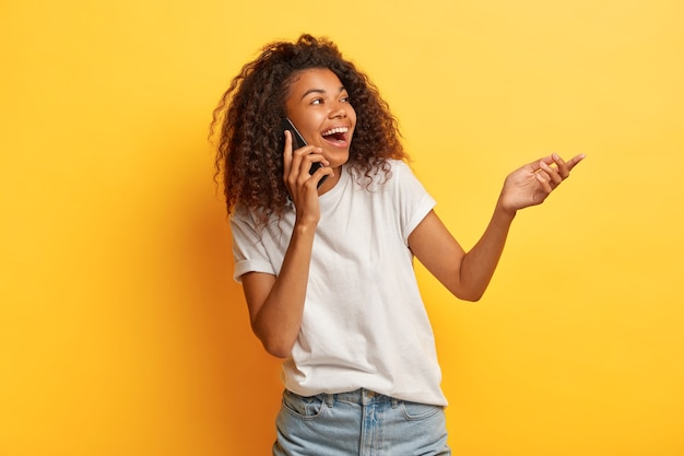 Overjoyed laughing curly haired woman enjoys funny conversation via cellphone, raises palm, focused on right side, wears casual outfit