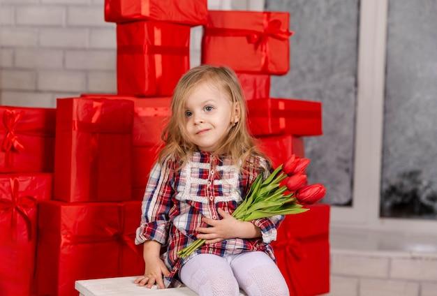 Обрадованная маленькая девочка держит кучу подарков на день святого валентина