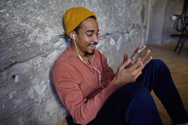 Uomo barbuto adorabile felicissimo con la pelle scura che indossa un maglione rosa, pantaloni blu, pantaloni e berretto senape, appoggiato al muro di cemento con il cellulare in mano